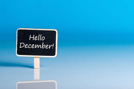 Hello december on sign at blue background with empty space for text, mockup. December 1st, the beginning of the Christmas and New Year holidays and sales