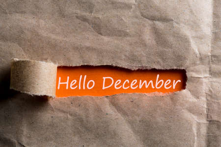Hello december inscription hiding in a tattered envelope. December 1, the beginning of the Christmas and New Year holidays and sales