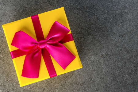 Gift trends. Thinking about new year, Christmas and valentine day gifts and online shopping. Yellow box present with bow. Mockup