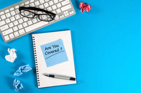 The words Are You Covered - written at notepad at workplace background. Asking the question, are you insured for your car, travel, home, health or other liability. Mockup