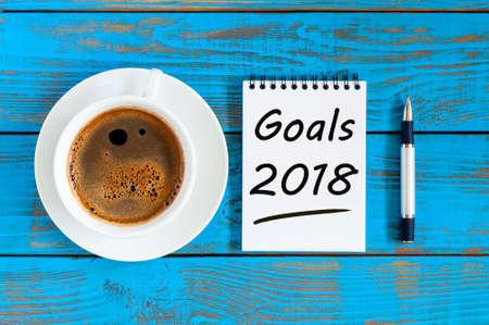 2018 목표 종이 노트 책 배경 및 푸른 나무 테이블에 모닝 커피 컵, 목표, 목표, 꿈 및 새해 내년 약속