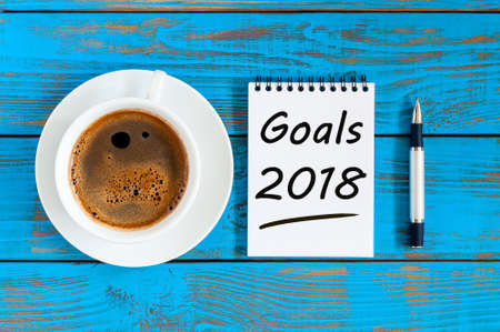 2018 goals on paper note book background and morning coffee cup on blue wood table, Targets, goal, dreams and New Years promises for the next year