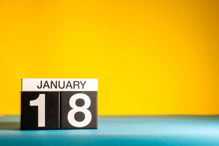 January 18th. Day 18 of january month, calendar on yellow background. Winter time. Empty space for text