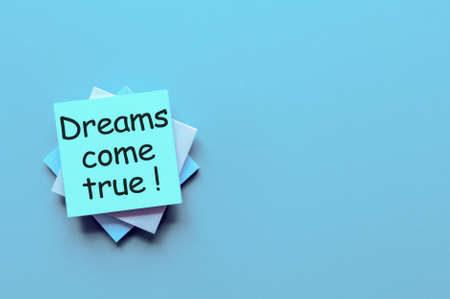 Hand writes Dreams come true - on light blue background with empty space for text and mock up