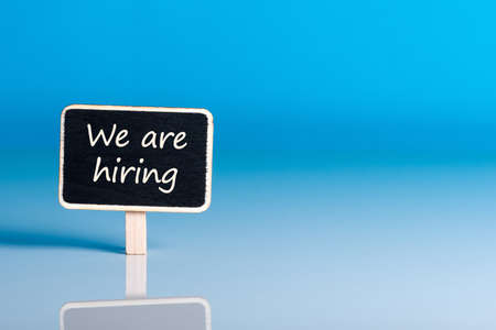 little wooden tag with message Were Hiring. Job offer open new way and give new opportunities Stock Photo