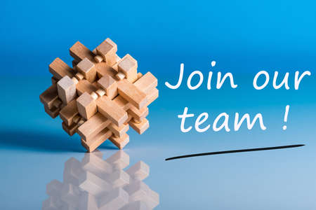 Job recruiting advertisement represented by JOIN OUR TEAM texts on blue background with wooden brain teaser talking about the difficult tasks, new challenges and opportunities