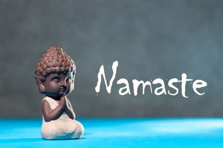 Close-up of little buddha meditating, focus on arms in Namaste gesture and text namaste - yoga and zen concept