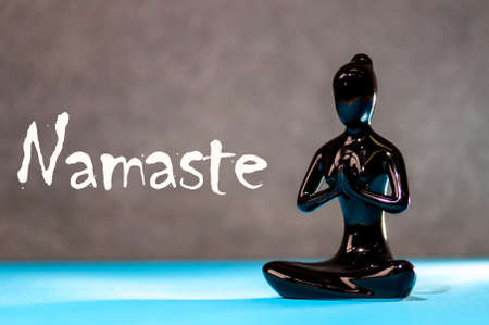 Little black figurine woman keep hands in Namaste - greeting sign. Yoga and meditation concept Stock Photo
