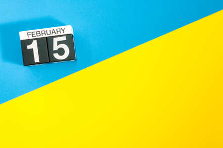 February 15th. Day 15 of february month, calendar on blue and yellow background flat lay, top view. Winter time. Empty space for text