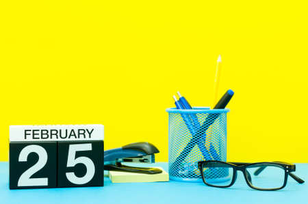 February 25th. Day 25 of february month, calendar on yellow background with office supplies. Winter time