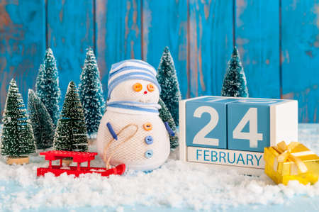 February 24th. Cube calendar for february 24 on wooden surface with snowman, sled, snow and fir Stock Photo