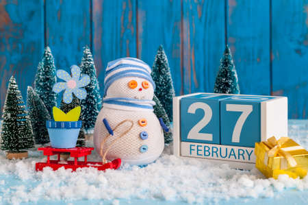 February 27th. Cube calendar for february 27 on wooden surface with snowman, sled, snow, fir and spring flower