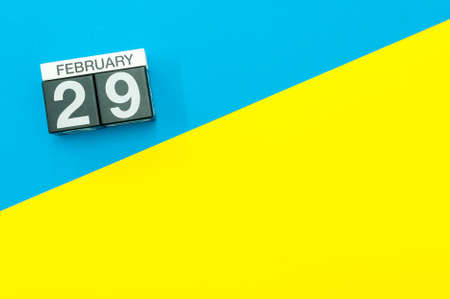 February 29th. Day 29 of february month, calendar on blue and yellow background flat lay, top view. Leap-year. Empty space for text 免版税图像