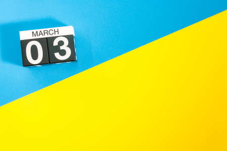 March 3rd. Day 3 of march month, calendar on blue and yellow background flat lay, top view. Spring time. Empty space for text