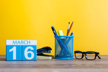 March 16th. Day 16 of march month, calendar on table with yellow background and office or school supplies. Spring time Stock Photo