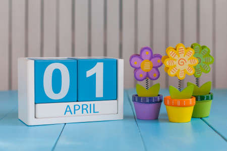 April 1st. Image of april 1 wooden color calendar on white background with flowers. Spring day, empty space for text. All Fools Day Stock Photo