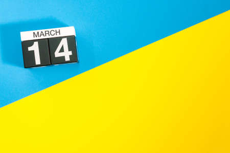 March 14th. Day 14 of march month, calendar on blue and yellow background flat lay, top view. Spring time. Empty space for text Stock Photo
