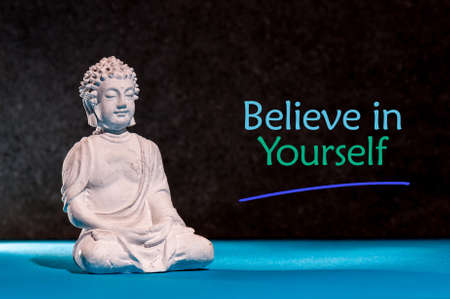 Believe in Yourself. Inspirational and motivating phrase near little buddha figurine Banco de Imagens