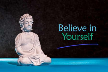 Geloof in jezelf. Inspirerende en motiverende zin in de buurt van kleine Boeddha beeldje