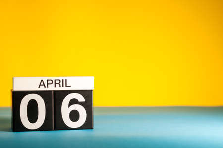 April 6th. Day 6 of april month, calendar on table with yellow background. Spring time, empty space for text Stock Photo