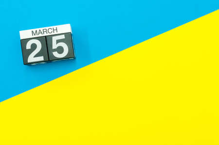 March 25th. Day 25 of march month, calendar on blue and yellow background flat lay, top view. Spring time. Empty space for text Stock Photo