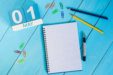 May 1st. Image of may 1 wooden color calendar on blue background.  Spring day, empty space for text.  International Workers Day
