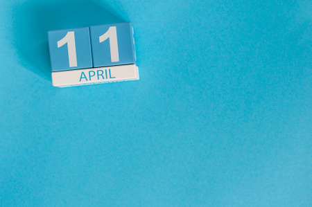 April 11th. Image of april 11 wooden color calendar on blue background.  Spring day, empty space for text. International Day Of Fascist Concentration Camps Prisoners Liberation