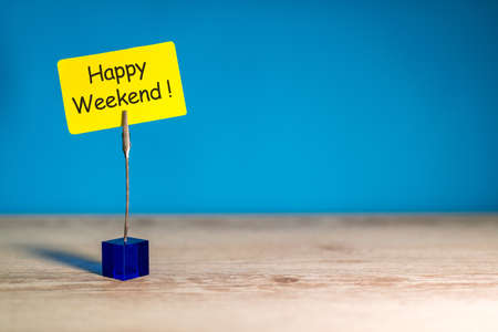 Happy Weekend words on little tag at work office place with empty space for text, template or mockup