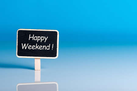 Happy Weekend words on little tag at blue background with empty space for text, template or mockup Banque d'images