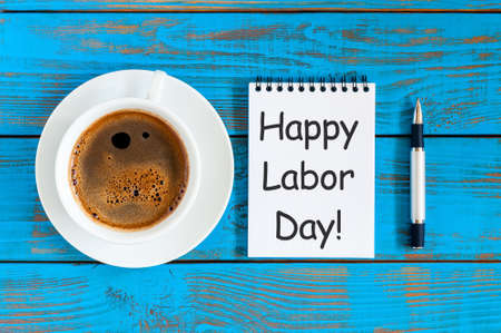 Happy labor Day - message in notepad at blue rustic table with morning coffee cup. Labour day celebrated at May 1. Spring time Фото со стока