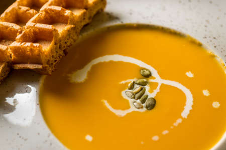 Hot pumpkin soup in white bowl with Belgian waffles. View from above, macro view