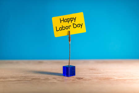 Happy labor Day - message on pinned yellow note at blue background. Labour day celebrated at May 1. Spring time Stock Photo