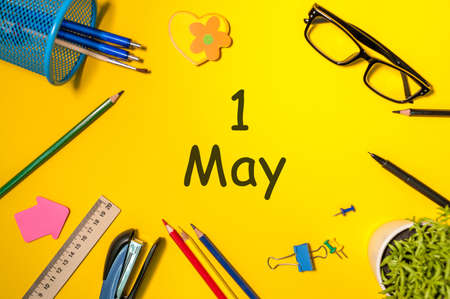 May 1st. Day 1 of month, calendar on business office table, workplace at yellow background. Spring time, Internationa labor Day