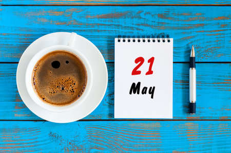 May 21st. Day 21 of month, tear-off calendar with morning coffee cup at work place background. Spring time, Top view Stock Photo