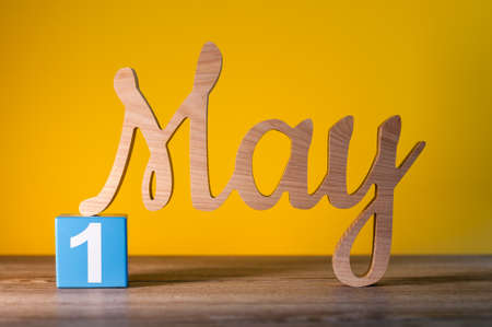May 1st. Day 1 of may month, calendar on yellow background with wooden carved letters. Spring time Stock Photo