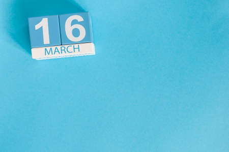 March 16th. Image of march 16 wooden color calendar on blue background.  Spring day, empty space for text