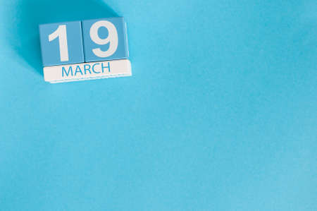 March 19th. Image of march 19 wooden color calendar with flower on blue background.  Spring day. Earth Hour and International clients Day
