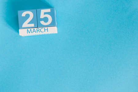 March 25th. Image of march 25 wooden color calendar on blue background.  Spring day, empty space for text.