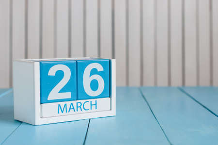 March 26th. Day 26 of month, wooden color calendar on white background. Spring time, empty space for text