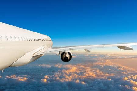 Passagiersvliegtuig in de blauwe lucht, uniek zijaanzicht. Vliegtuigen die boven de cumuluswolken vliegen. Vliegtuig reizen concept Stockfoto