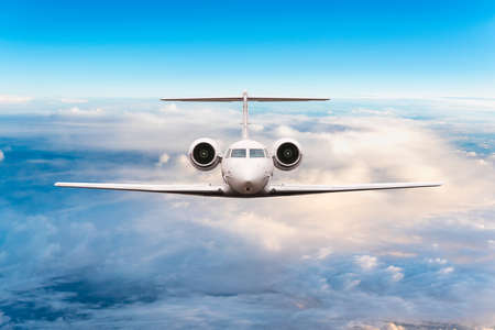 Front view of aircraft. Privat jet in flight. The passenger plane flies high above the clouds and blue sky. Luxury travel concept Stock Photo