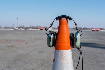Headphones of aircraft technician, who conducts preflight preparation of the aircraft, are put on an orange cone. Technician checking engine of civil airliner concept Stock Photo