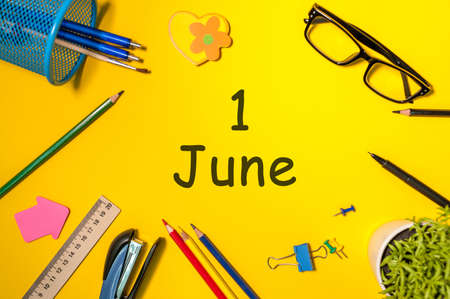 June 1st. Day 1 of june month, calendar on yellow background with office suplies, Top view. Summer day at work