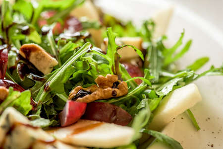 Leaf vegetable salad with cheese, grapes, walnuts and tasty sauce. Healthy, diet food