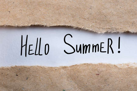 Hello Summer - text on torn brown envelope background Stock Photo