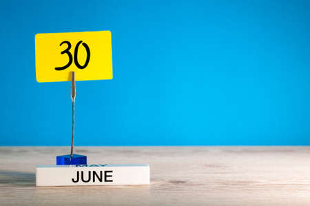 June 30th. Day 30 of june month, calendar on table with blue background. Summer time, empty space for text or template.