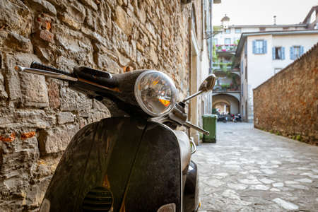 Typical street scene in Italy with a black scooter or moped on an old narrow cobblestoned street. Travel concept