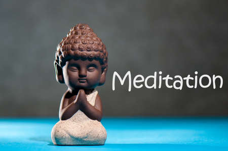 Meditation and yoga concept. Picture of a meditating little buddha