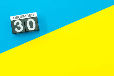 December 30th. Image 30 day of december month, calendar on blue-yellow background with empty space for text, mockup