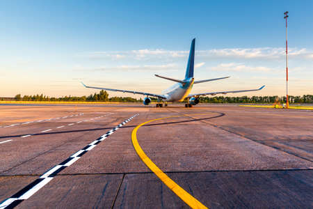 Commercial airplane taxied on the airport platform and is preparing to take off. Taxiways and a plane at sunset. Travel by aircraft concept Reklamní fotografie